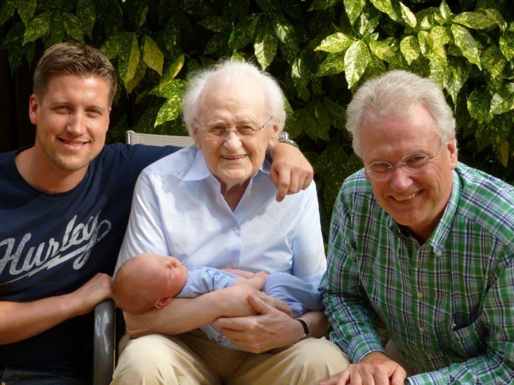 Homens de diferentes gerações: Um adulto, um idoso segurando um bebê, e um homem de meia idade.