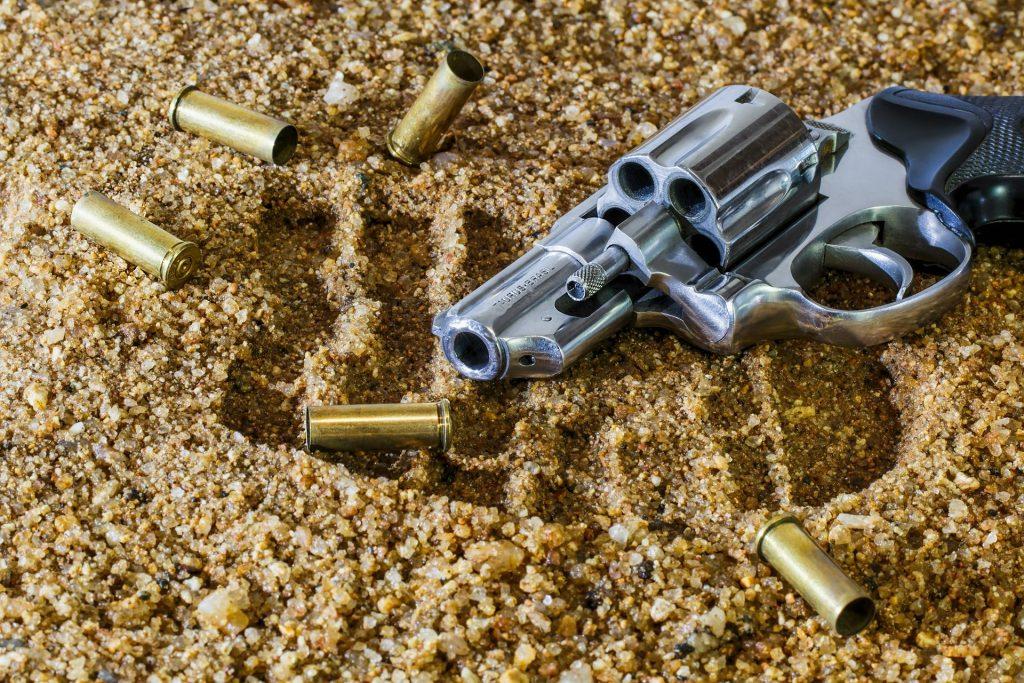 Arma de fogo sobre uma areia cheia de pedras. Ao lado da arma várias balas de fogo.