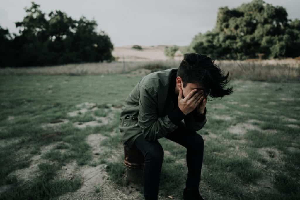 Homem em um gramado com as mãos em seu rosto