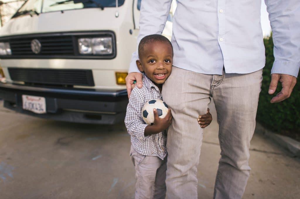 Criança segurando bola de futebol e abraçando perna do pai.