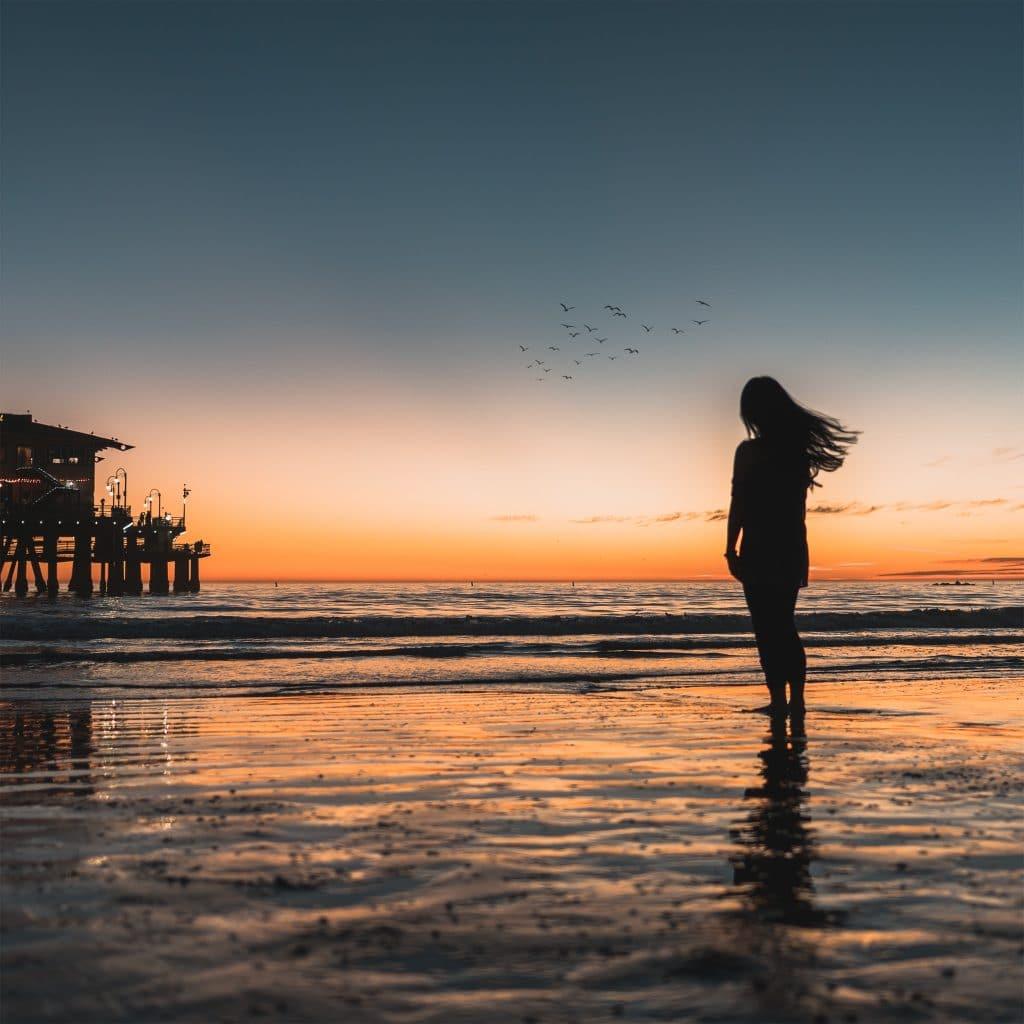 Mulher descalça andando no mar e olhando para o horizonte