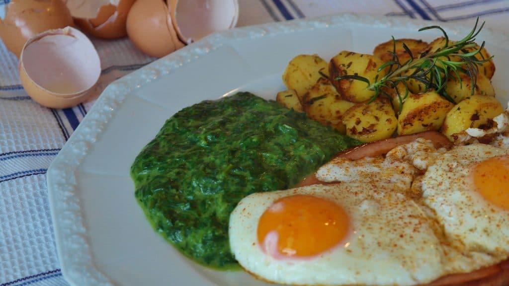 Creme de espinafre servido com ovos fritos e batas assadas com alecrim.