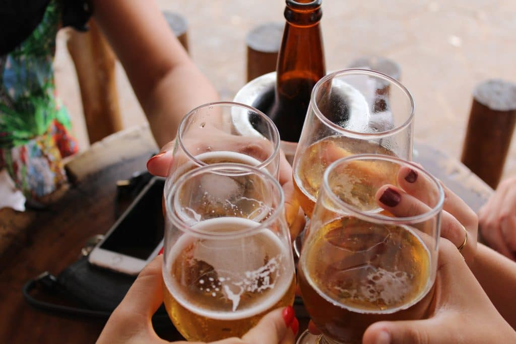 Brinde de copos de cerveja em mesa de bar