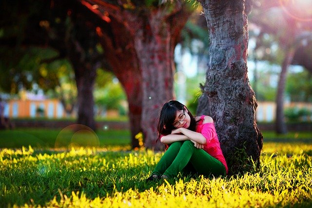 Garota sentada em gramado encostada em árvore pensativa