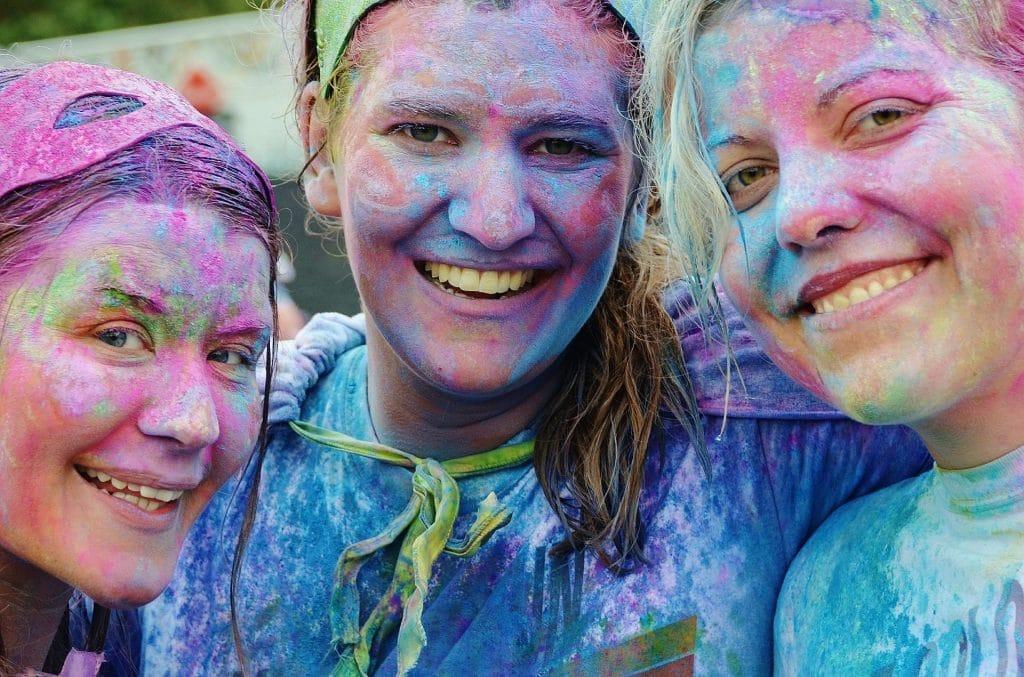 Três garotas sorrindo. Todas estão com o rosto pintado e colorido. Imagem de GLady por Pixabay.