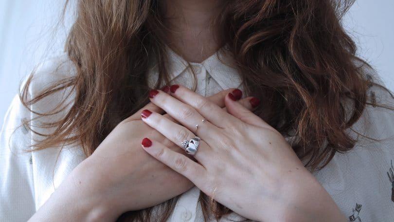 Mulher com camisa de botões coloca as mãos sobre o peito.