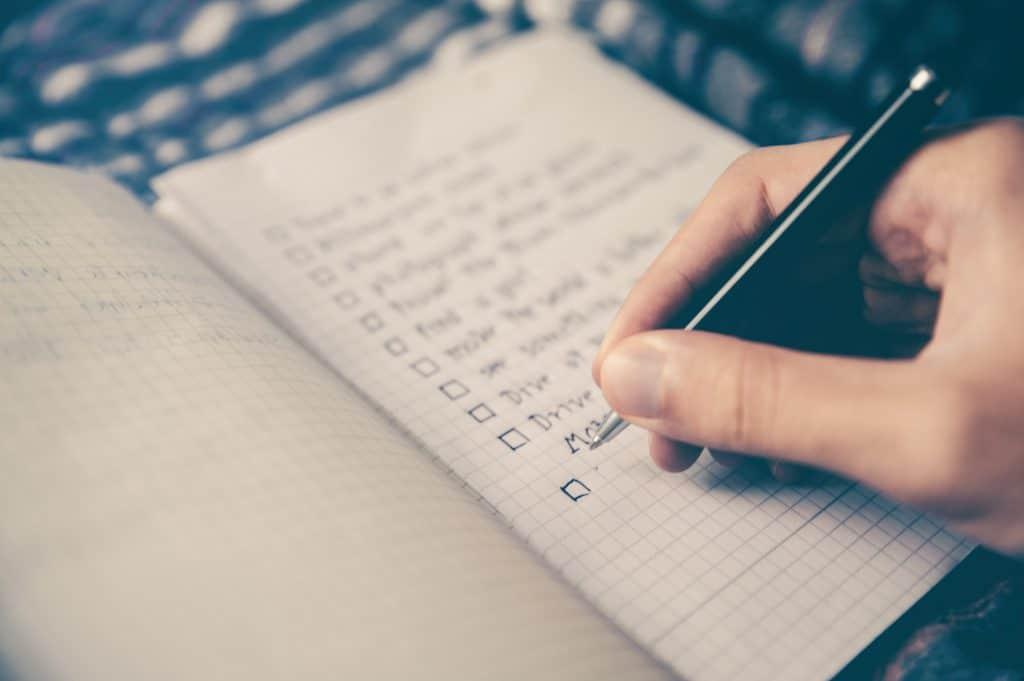 Pessoa escrevendo, em um caderno quadriculado com uma caneta, uma lista de afazeres.