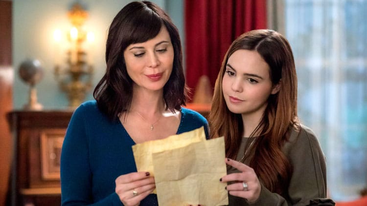 Duas mulheres na sala, uma ao lado da outra, segurando uma carta e lendo.