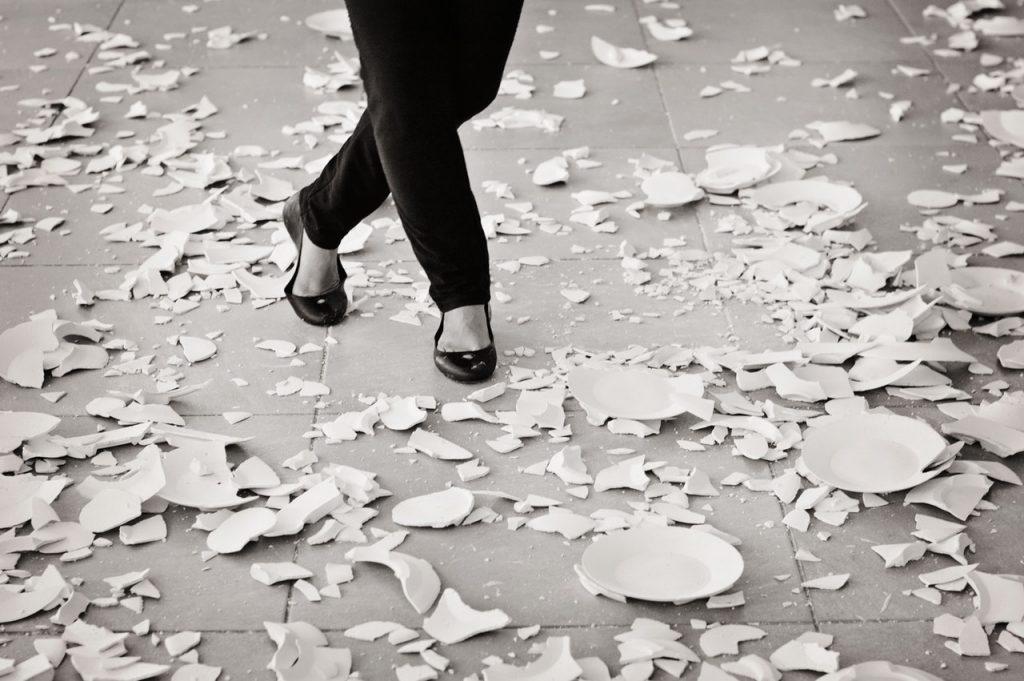 Mulher caminhando sobre chão coberto de pratos quebrados.
