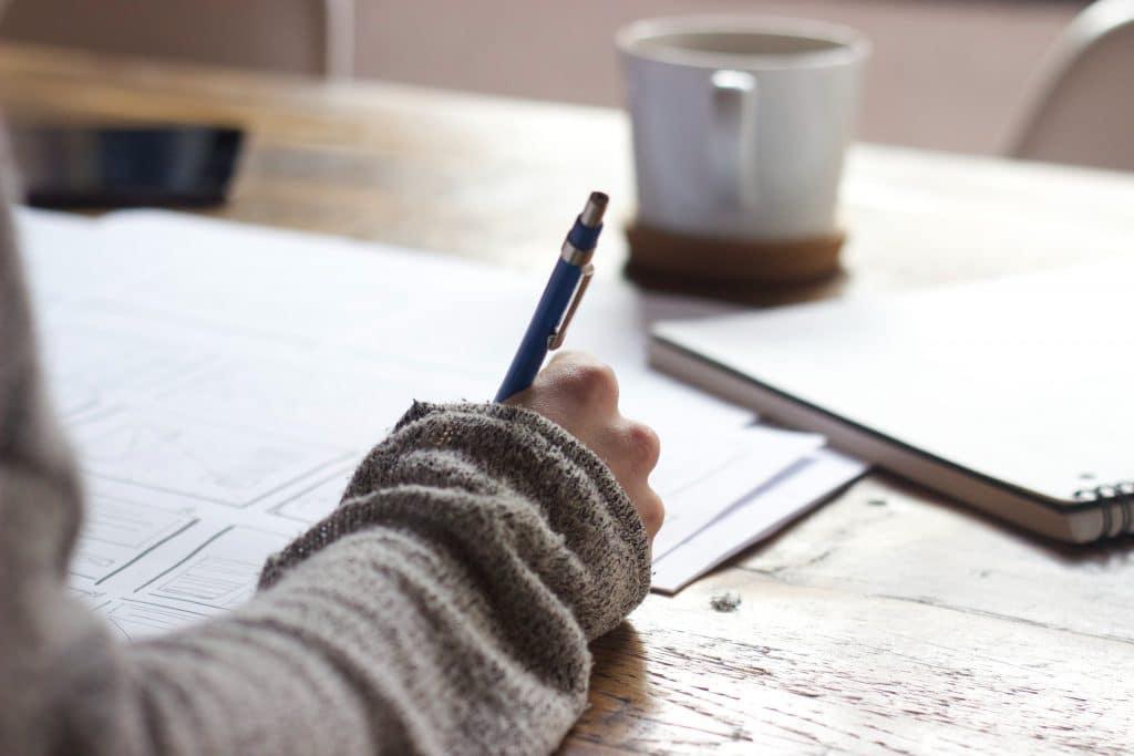 Pessoa escrevendo em folhas