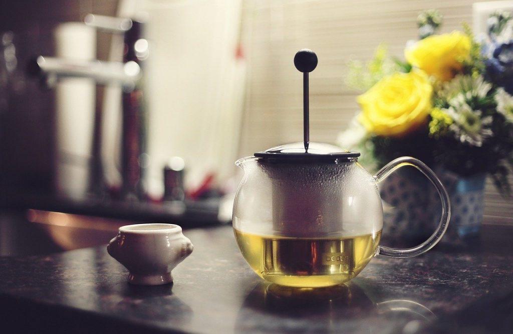 Jarra com chá sobre uma mesa de pedra, ao lado de um pequeno recipiente e de flores em um vaso.