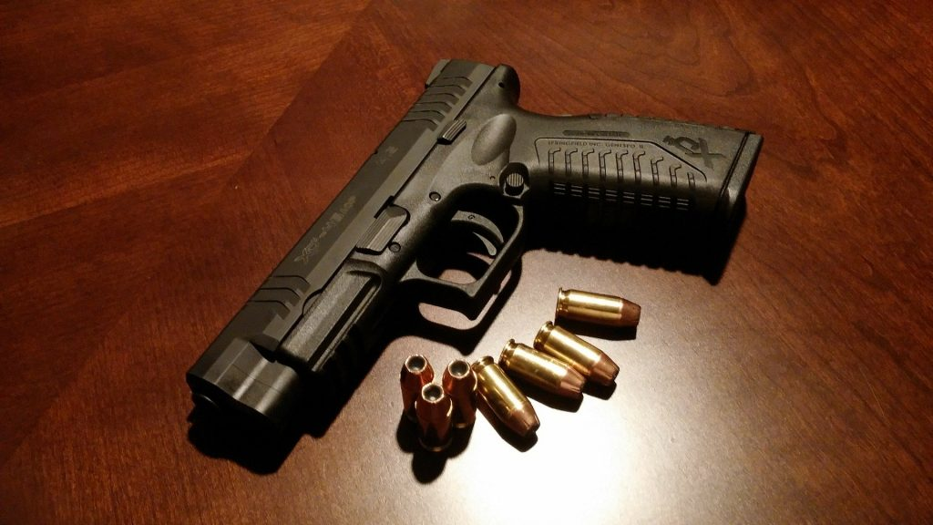 Arma de fogo sobre uma mesa de madeira escura. Ao lado da arma, sete balas.