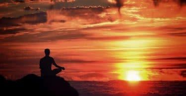 Pessoa sentada com as pernas cruzadas em uma montanha durante o nascer do sol.