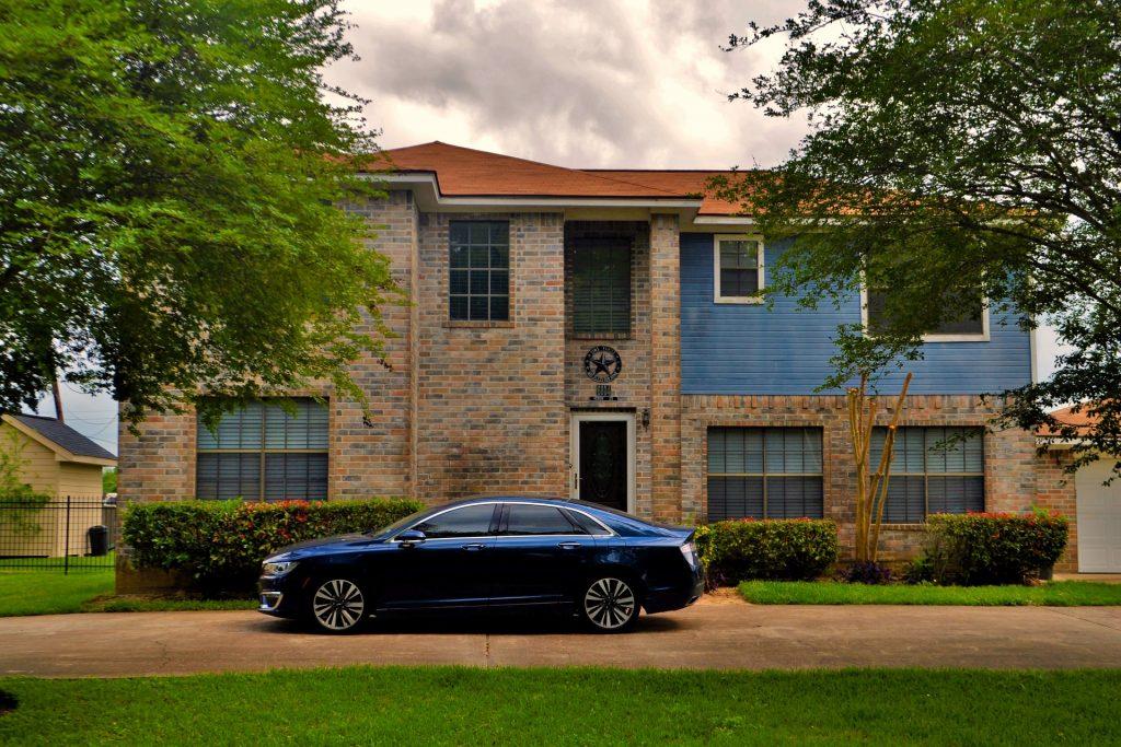 Frente de uma casa já construída. Na porta da entrada um lindo carro azul.