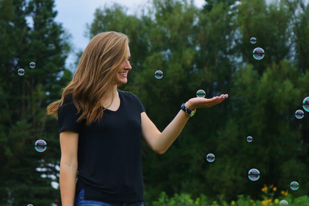 Mulher feliz entre bolhas de sabão