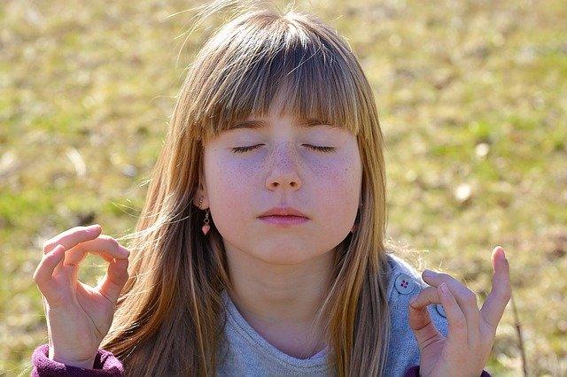 Criança de olhos fechados meditando