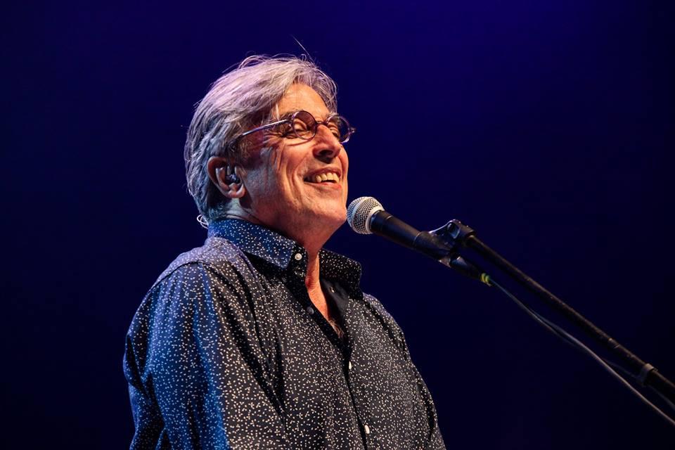 Fotografia de Ivan Lins cantando em um microfone enquanto sorri.