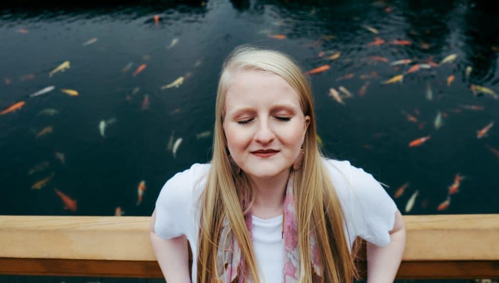 Mulher em ponte de olhos fechados com peixes ao fundo nadando