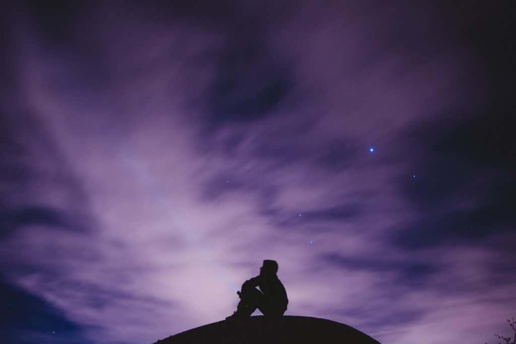 Silhueta de um homem sentado observando o céu à noite.