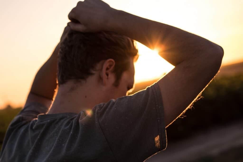 Homem de costas com mão na cabeça e sol refletindo ao fundo