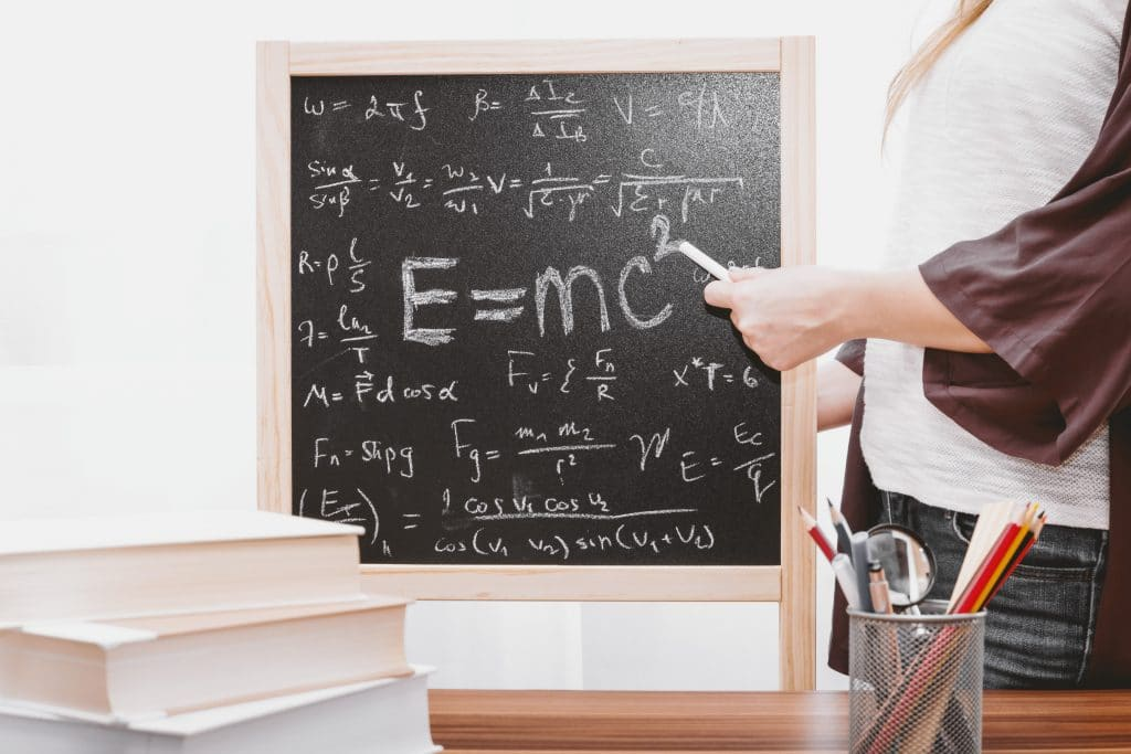 Mulher fazendo cálculos na lousa.