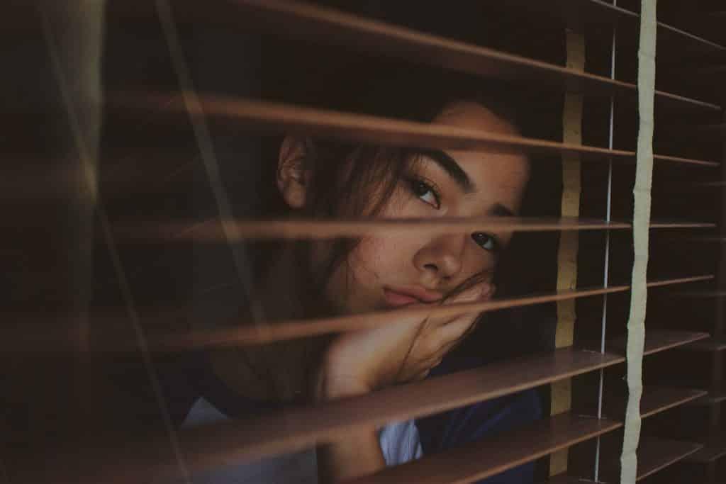 Mulher apoiada na janela olhando para o lado com tristeza