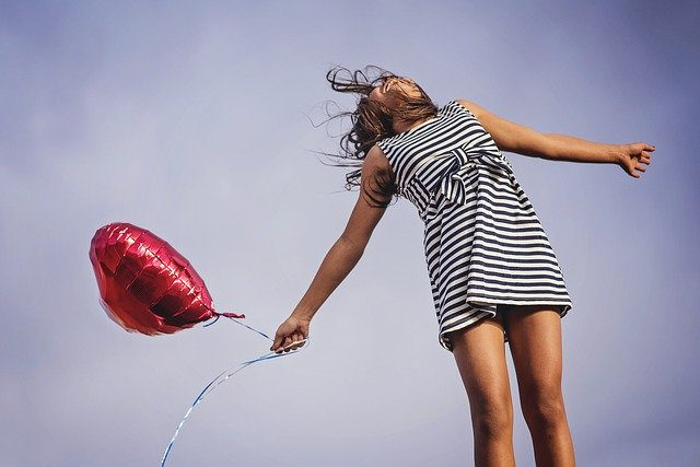 Garota segurando balão de coração com braços abertos vista de baixo