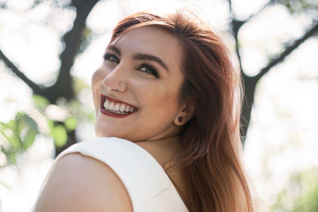 Fotografia de Ju Romano sorrindo em um parque, durante o dia.
