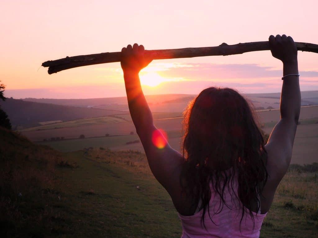 Mulher segurando um graveto para o alto.