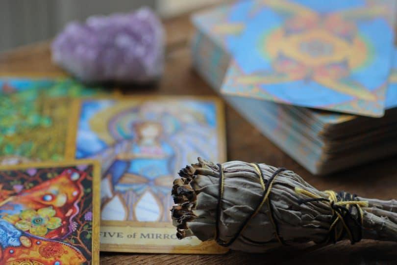 Cartas do tarot e cristal com seda queimando