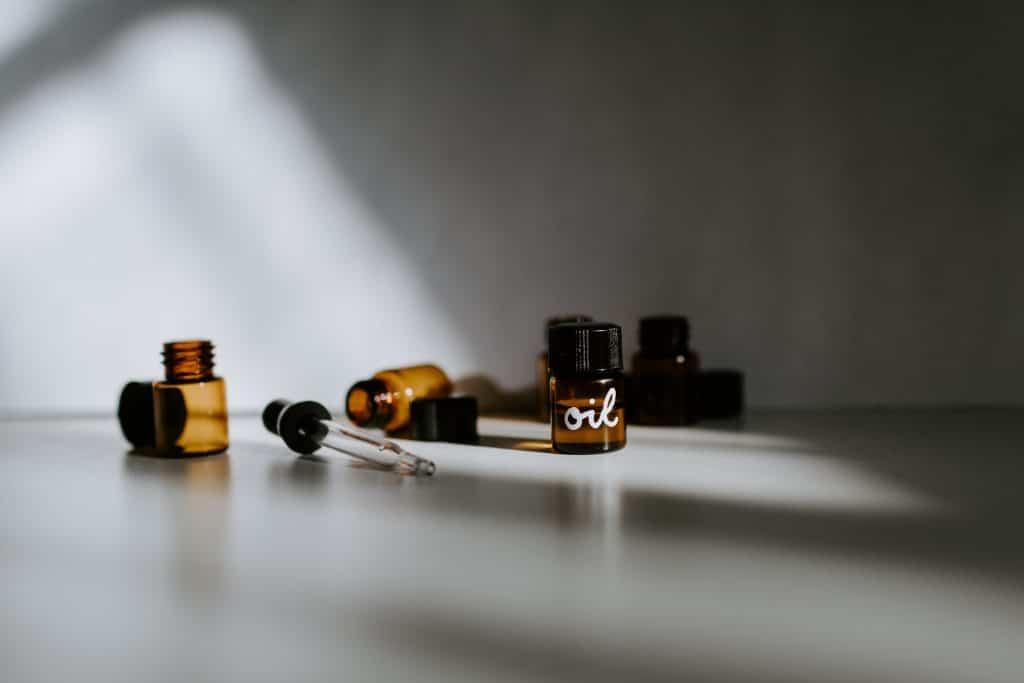 Pequenos frascos com diferentes tipos de óleos sobre uma mesa.