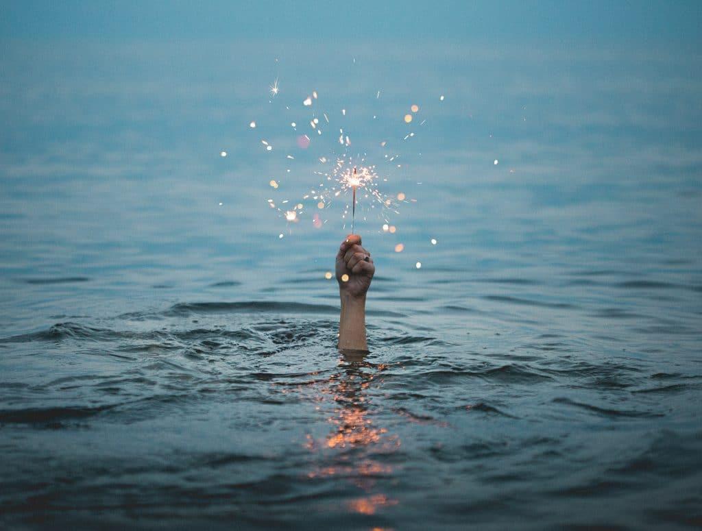 Mão saindo da água segurando velinha de luz acesa
