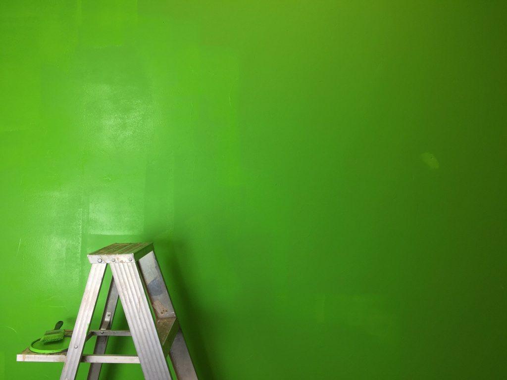 Parede pintada na cor verde. Ao lado uma escada, um pincel e a tampa da lata de tinta.
