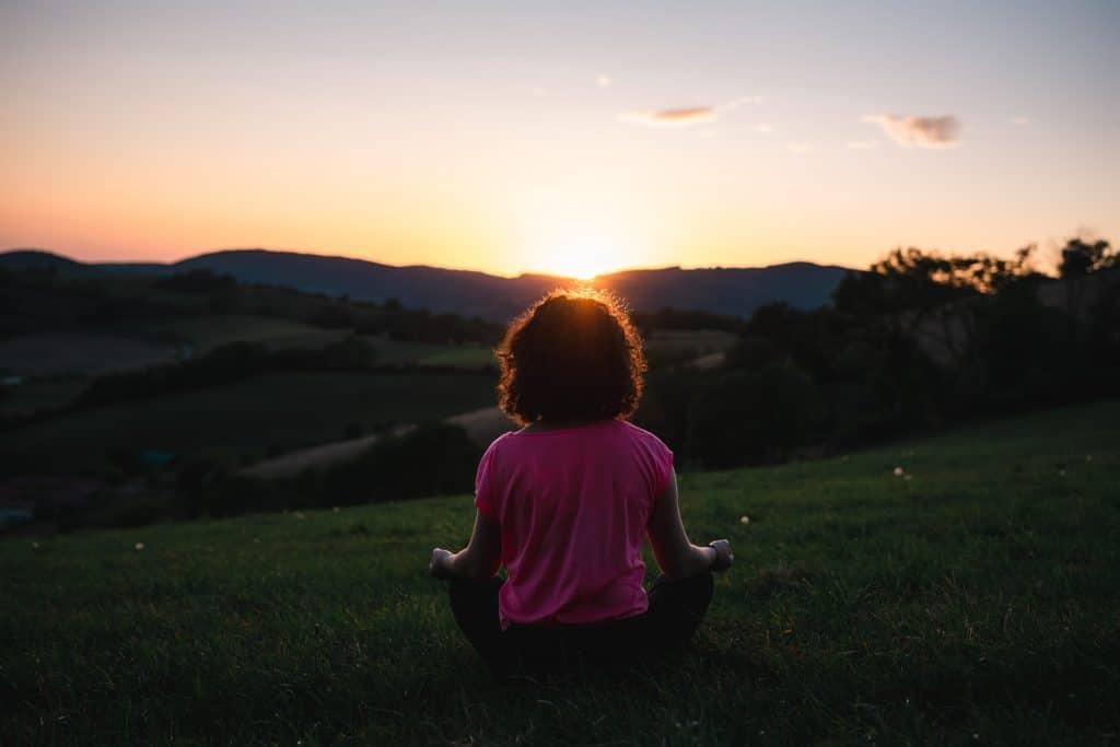 Mulher meditando em um campo aberto.