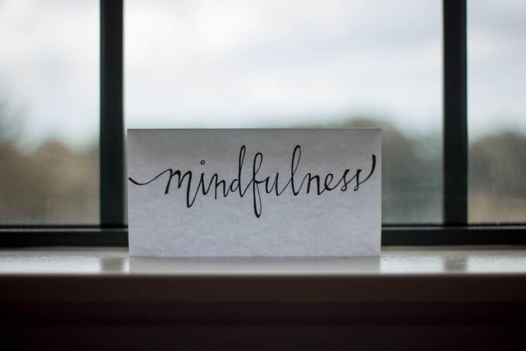 """Plaquinha na escrito """"Mindfulness"""" em frente a janela"""