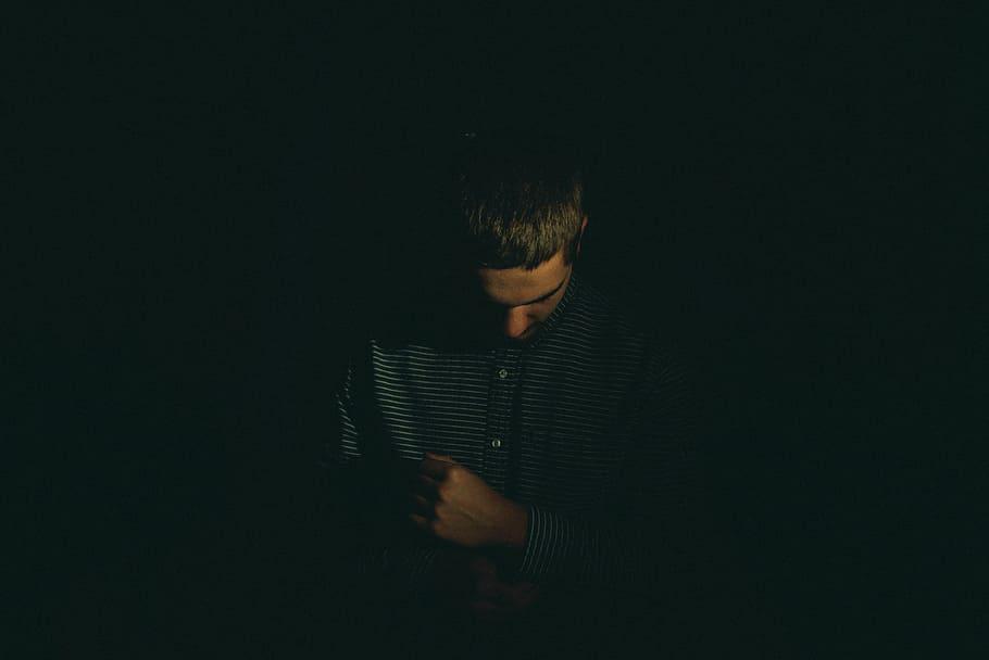Homem de pé com a cabeça inclinada para baixo e vestindo uma camisa. A luz nele é bem fraca, e a sua volta está completamente escuro.