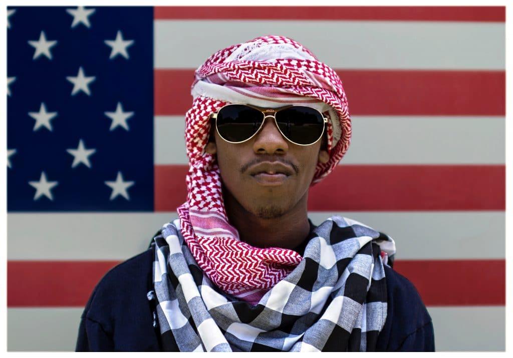 Homem negro usando óculos escuros e um traje muçulmano em frente à bandeira dos Estados Unidos da América.