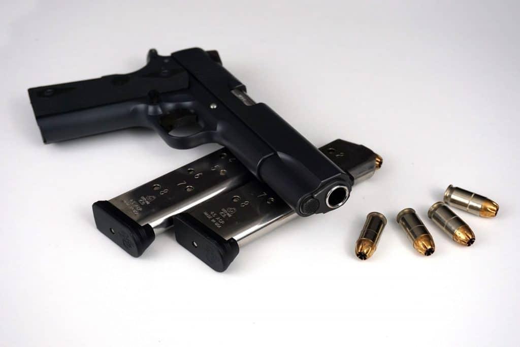 Arma de fogo na cor preta colocada sobre dois pentes de bala. Ao lado, quatro balas.