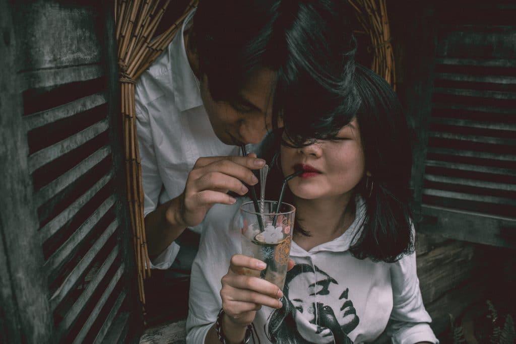 Casal tomando suco com canudinhos no mesmo copo