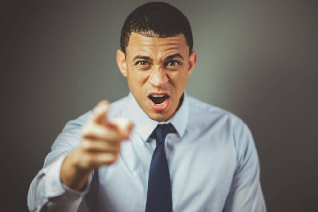 Homem gritando e apontando o dedo para frente