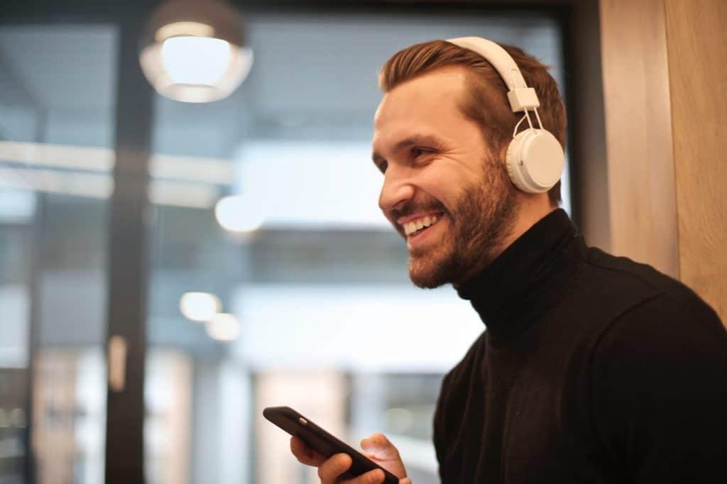 Homem usando fones de ouvido e segurando um celular enquanto sorri.