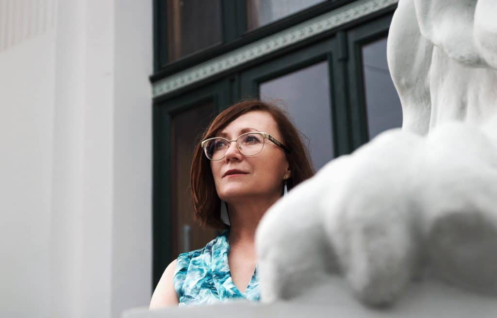 Mulher de meia idade e cabelos lisos, de óculos, olhando para cima em frente a uma construção urbana.