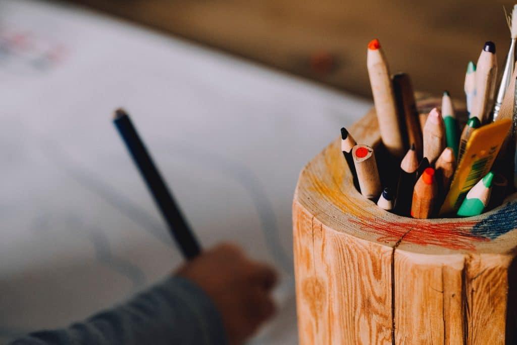 Criança desenhando com lápis de colorir
