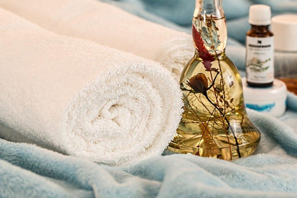 Frasco com essências naturais ao lado de toalhas lisas sobre um pano macio.