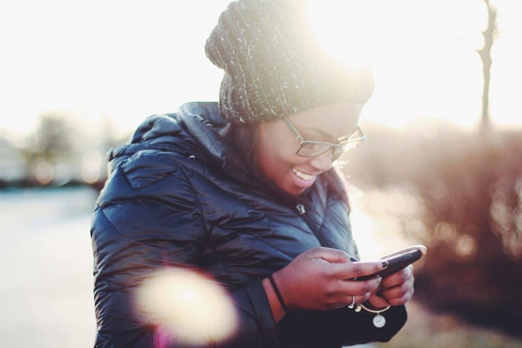 Mulher com celular na mão sorrindo e sol refletindo