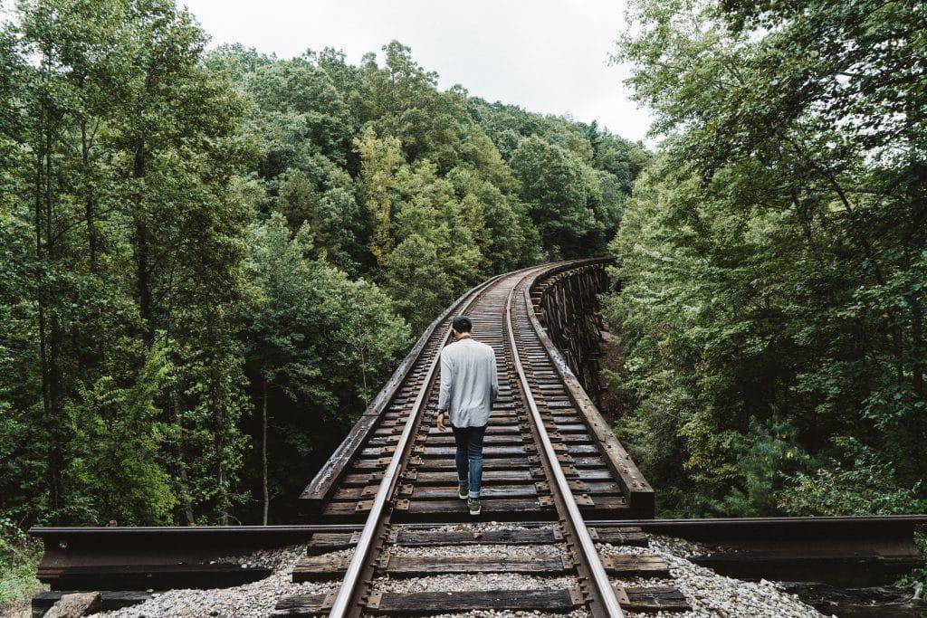 Homem andando nos trilhos de trem