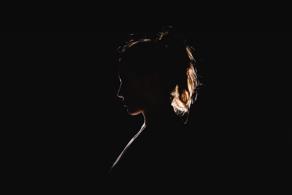 Mulher no escuro com uma luz vindo por trás em seu cabelo