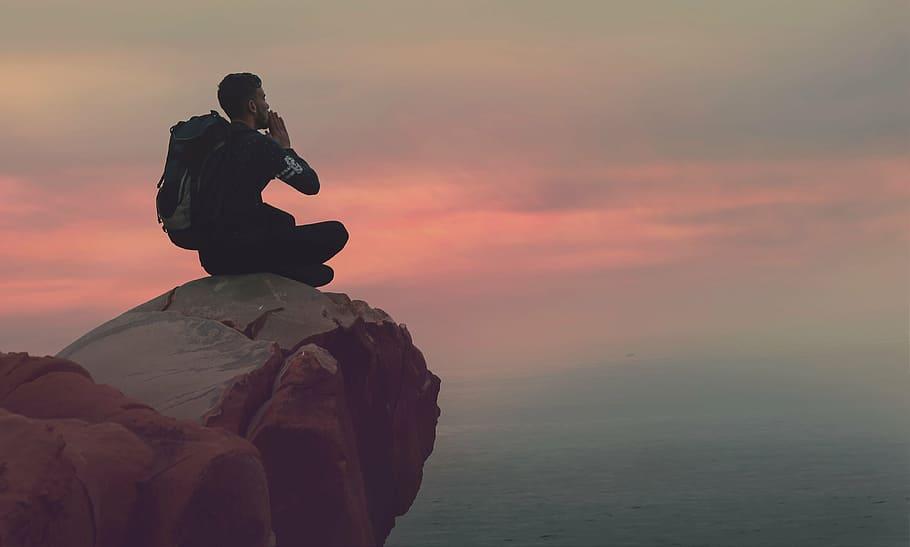 Homem sentado com as pernas cruzadas em uma pedra no topo de uma montanha. Ele tem uma mochila nas costas, durante o pôr do sol.
