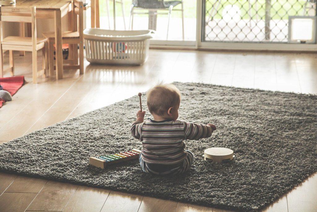 Imagem de um bebê sentando no chão em um tapete cinza em uma sala bem ampla. Ele está brincando com vários  instrumentos musicais.