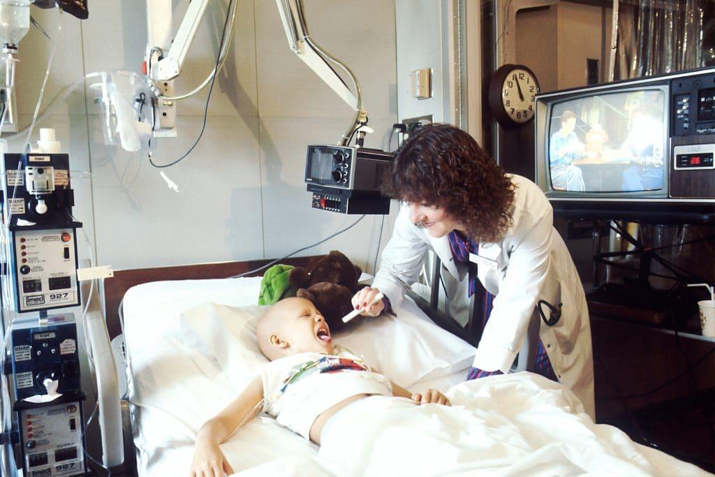 Criança vítima de câncer deitada em uma maca de hospital enquanto é examinada por uma médica, que aponta uma lanterna para dentro de sua boca.